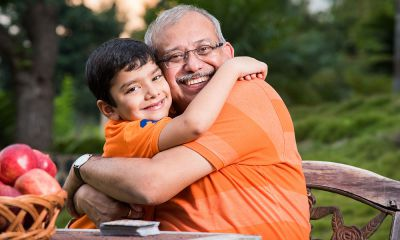 Grandfather hugging young grandson wearing orange t-shirts