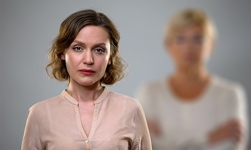 woman looks at camera with sombre expression