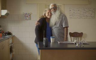elderly Aboriginal man and woman hugging in a kitchen