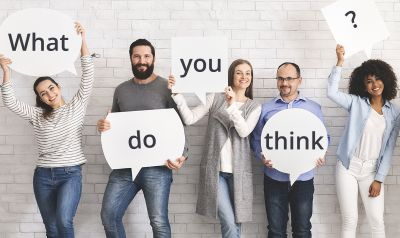 People holding speech bubbles that say what do you think