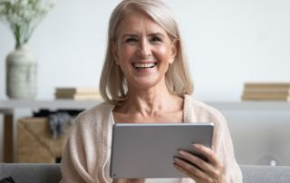 Woman smiling and holding an ipad