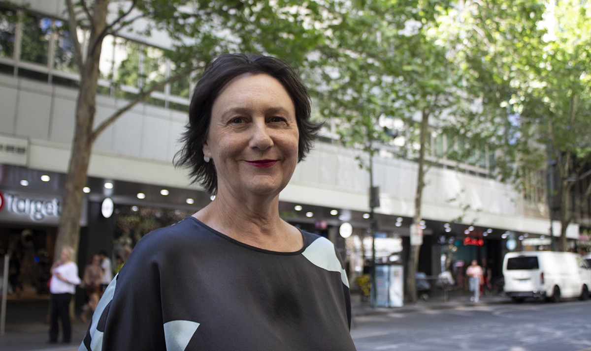 Close-up of Catherine Fraser standing in a Melbourne street under trees