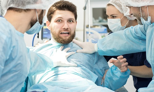 Humorous Man on operating table looking frightened surrounded by medical staff