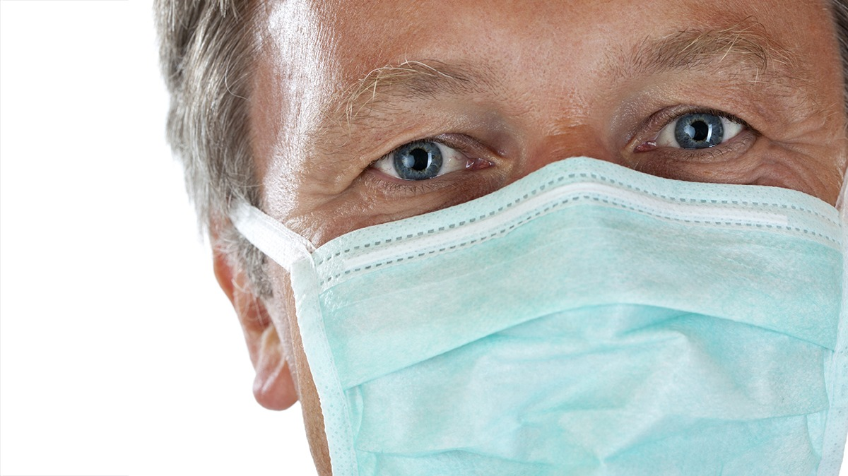 Close up of doctor wearing surgical mask looking at camera