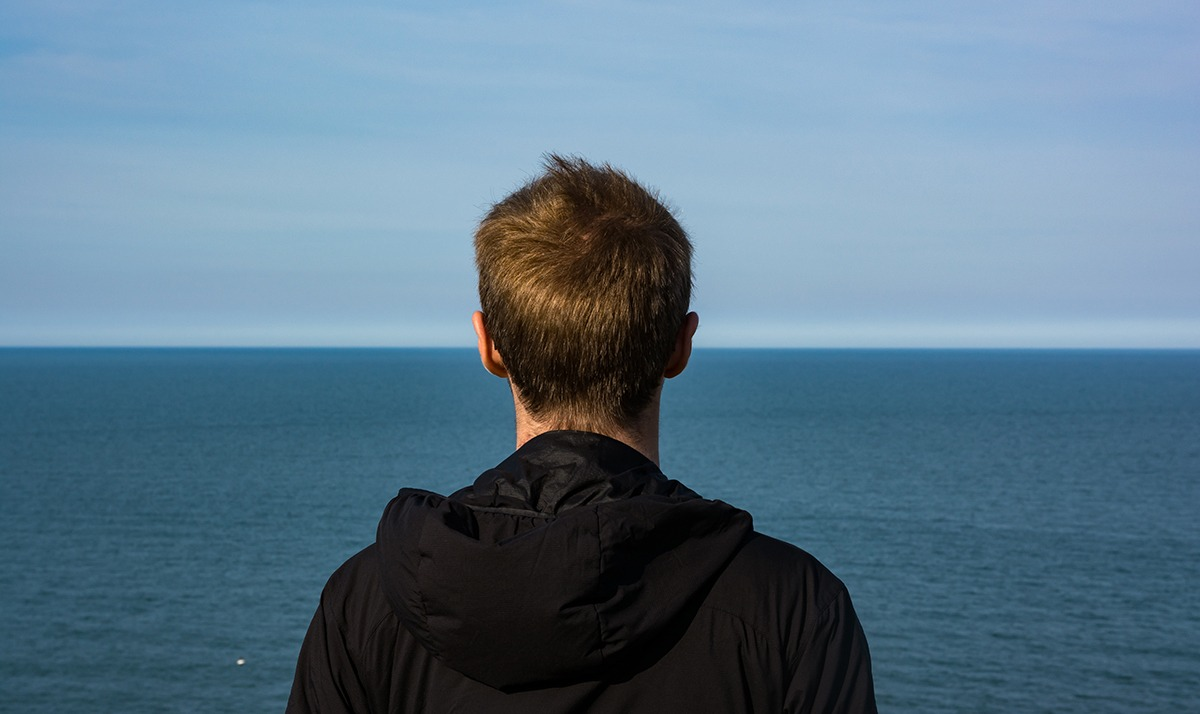 Man standing with back to camera staring at ocean