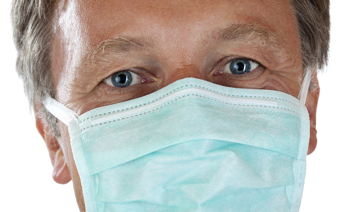 Doctor in blue surgical mask looking at camera