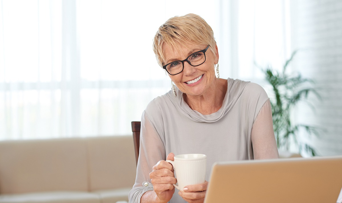 woman smiling at camera while holding a coffee mug and sitting in front of a laptop computer