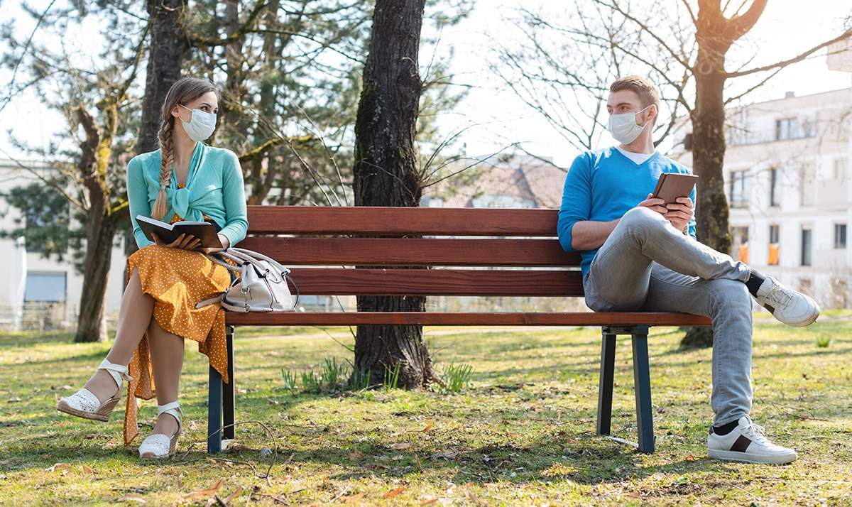 Two people sitting at opposite ends of a park bench wearing medical face masks