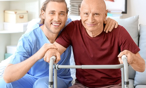 A young health support worker in blue scrubs sits with his arm around his patient. His patient is an older balding man wearing a burgundy shirt and holding a walking frame. They are both smiling and looking at the camera